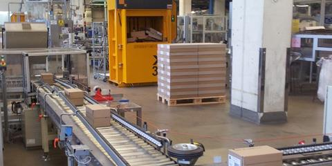 Cardboard boxes on assembly line with yellow baler in the background