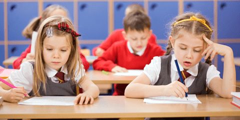 Children sit at school desks writing