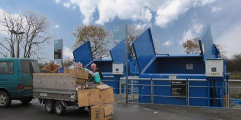 Man loads cardboard boxes of trailer over into compactor