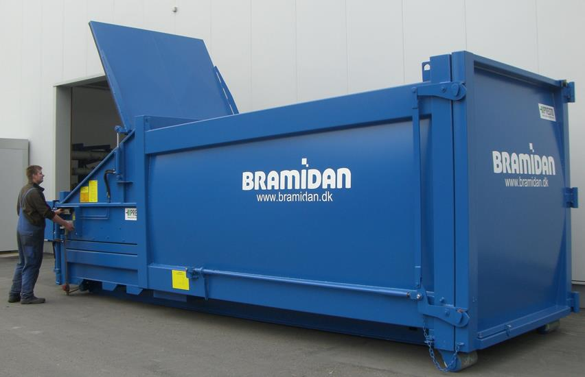Man operates blue compactor placed outside