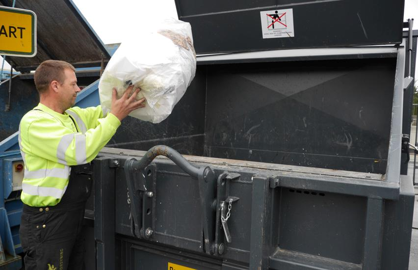 Man in overalls fills in plastic in grey compactor