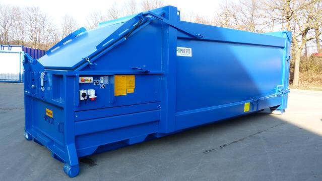 Blue compactor in yard, with roll on roll off container