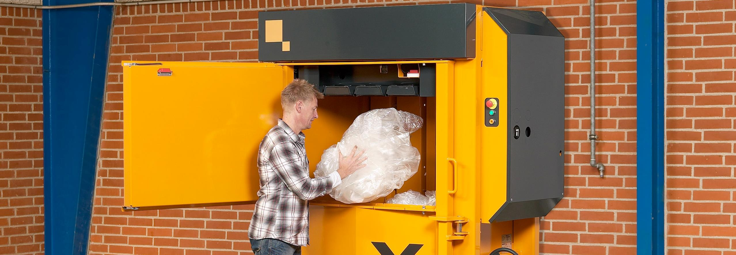 Man fills plastic waste into yellow baler