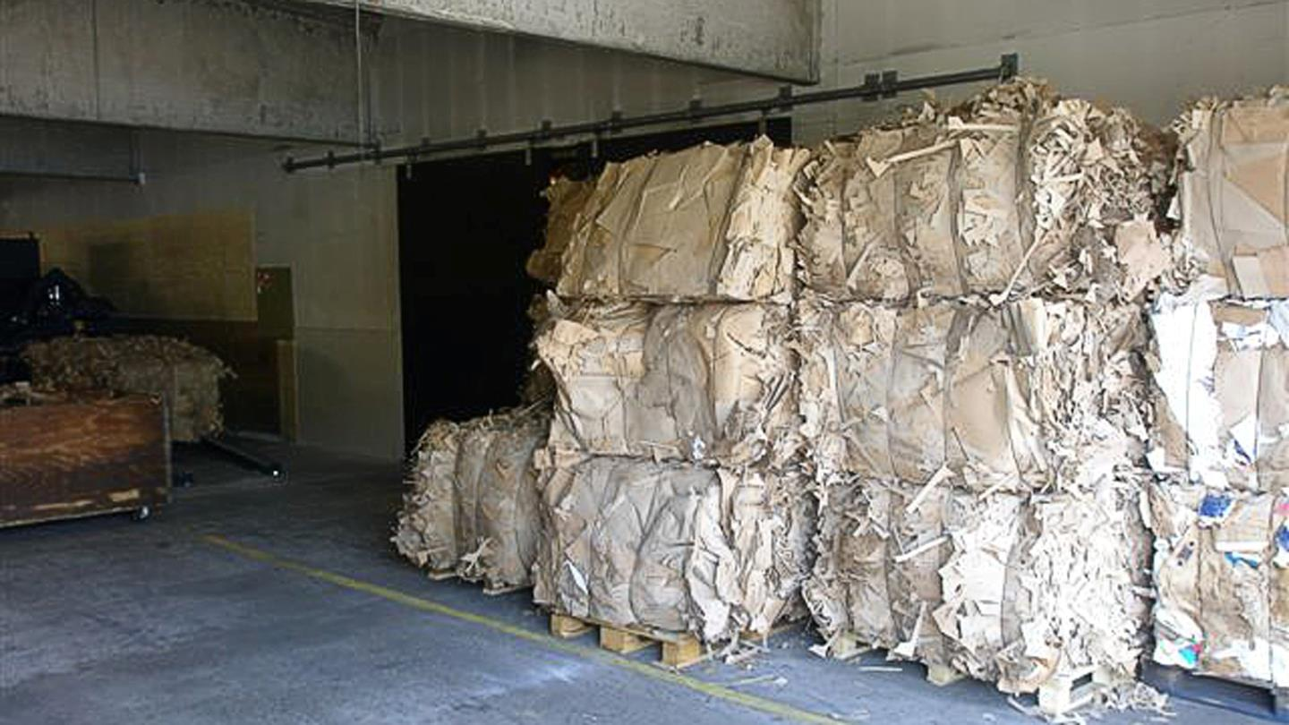 Bales of cut cardboard stacked in storage room