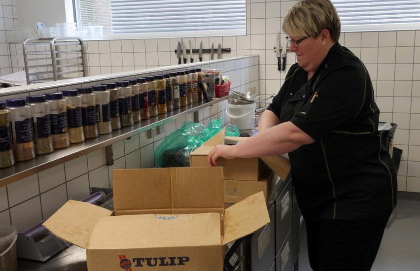 Canteen employee opens cardboard boxes with groceries