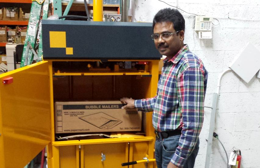 Employee at Marshal Wallets puts cardboard box into Bramidan B3 baler