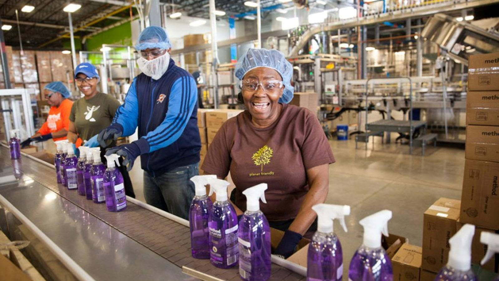 People wearing hairnet at assembly line with purple soap bottles
