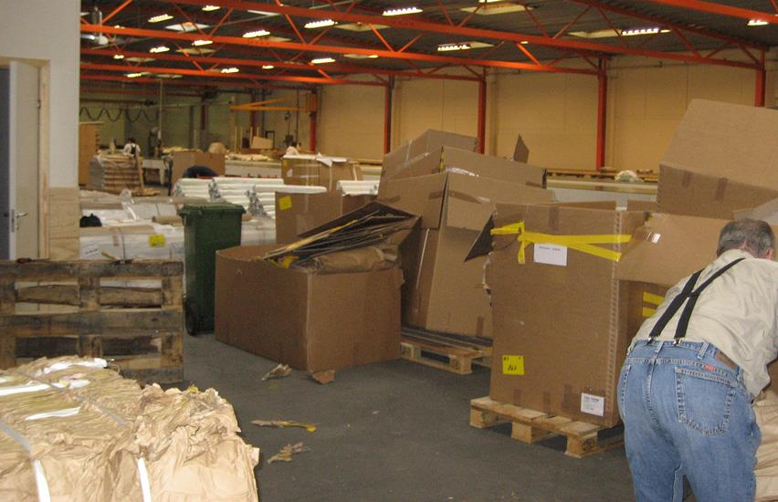 Man inside warehouse at Rewair, between a lot of cardboard boxes