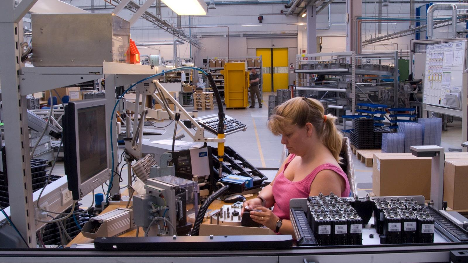 Blond woman in pink blouse working at assembly line at Sauer-Danfoss
