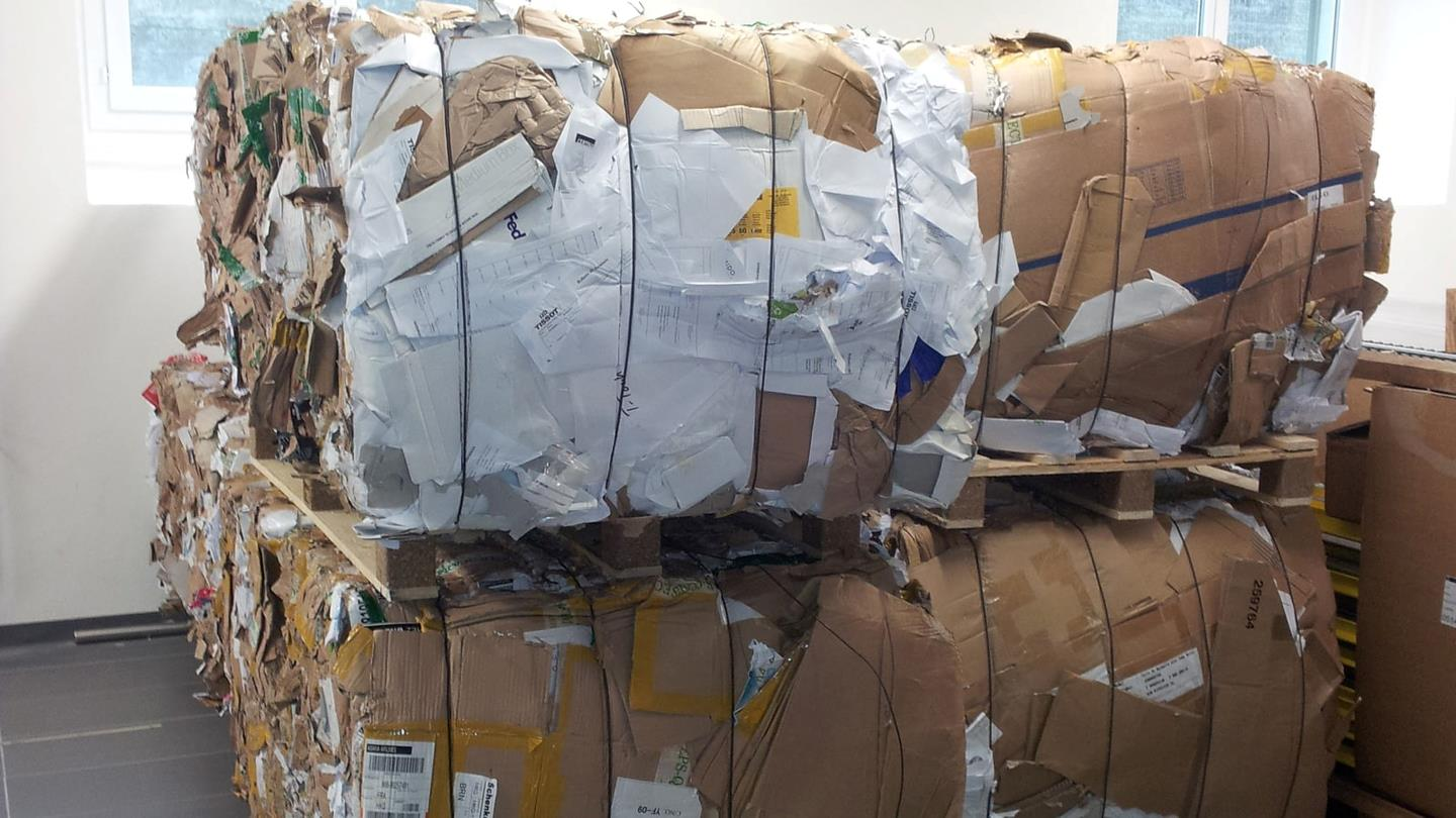 Compressed cardboard bales tied with steel wires stacked in Tissot warehouse