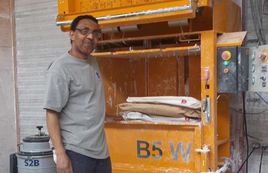 Nitta employee in front of baler with vertical door. Compacted dusty bags are indside the chamber.