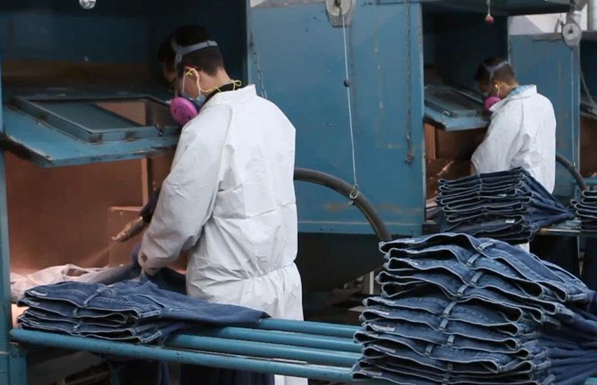 Two employees working with jeans production