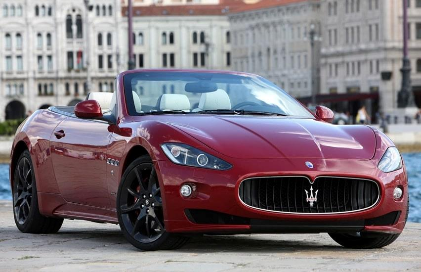 Red Maserati sports car with white leather seats parked in front of beautiful old buildings