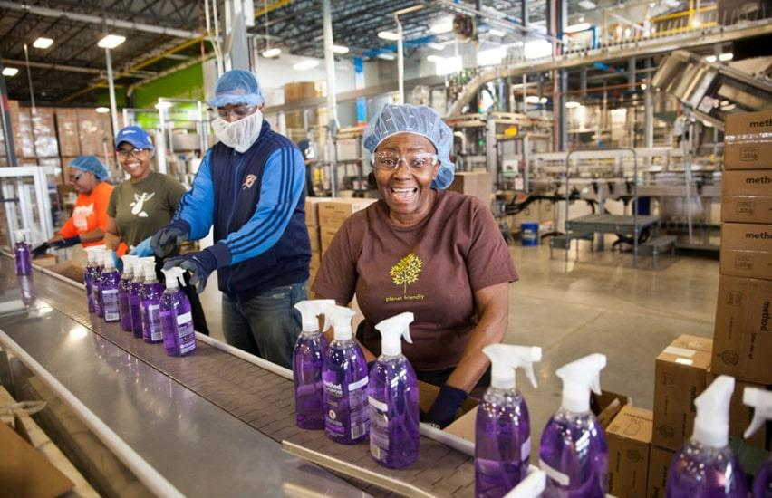 Staff at Method Home with hair nets at assembly line with purple spray bottles