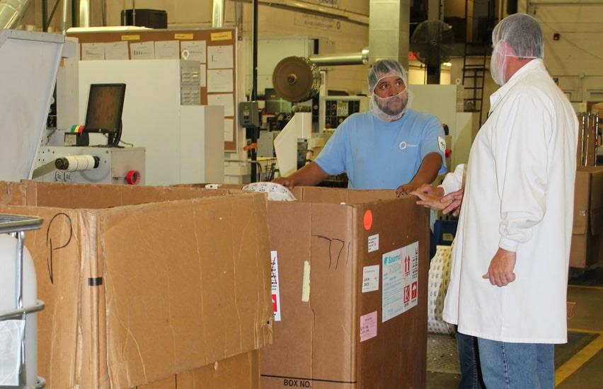 Employees in industrial clothes next to big cardboard bulk boxes